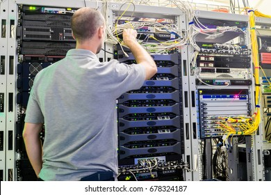 Senior Engineer works near the racks with server equipment. Man is  on the main technical platform of the Internet provider. Technical Support Engineer is  in the data center server room