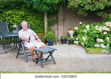 Senior enjoying a beer in his back garden on a sunny day