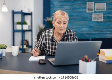 Senior entrepreneur reading from portable computer without glasses. Elderly woman in home living room using moder technoloy laptop for communication sitting at desk indoors.