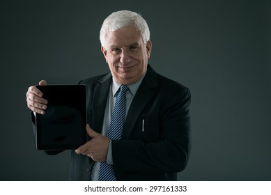 Senior entrepreneur smiling and showing digital tablet: technology in business concept