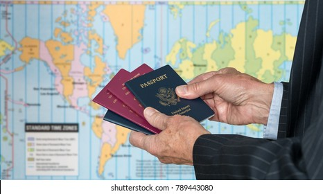 Senior executive hand holding USA and UK passports against blurred background of world map of timezones