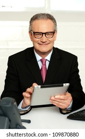 Senior executive sitting with tablet pc in hands and smiling at camera