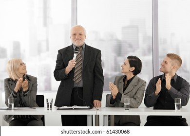 Senior executive standing, giving speech with microphone, sitting colleagues clapping and smiling.