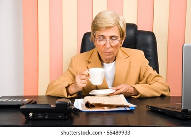Senior executive woman with glasses reading news and drinking coffee
