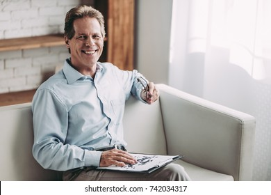 Senior experienced psychologist is sitting on sofa in his office and smiling.