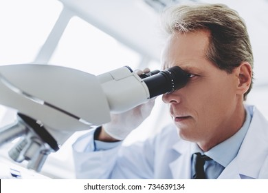 Senior experienced scientist is working in laboratory. Doing investigations with microscope.