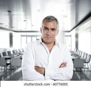 senior expertise gray hair businessman posing interior white modern office [Photo Illustration]