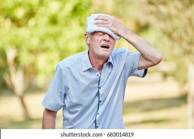 Senior fainting man cooling his head with wet cloth