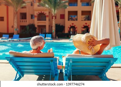 Senior family couple relaxing by swimming pool lying on chaise-longues. People enjoying summer vacation.
