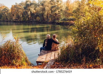 Senior family couple relaxing by autumn lake. Man and woman enjoying nature and hugging sitting on pier