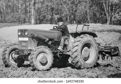 Senior farmer driving a ancient and rusty tractor on field. Land farming and cultivation in Romania. Vintage picture.