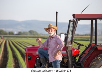 Senior farmer with straw hat standing beside small tractor in field