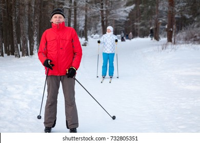 Senior father with adult daughter skiing on cross-country skis in winter forest