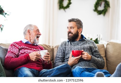 A senior father and adult son sitting on a sofa at home at Christmas time, talking.