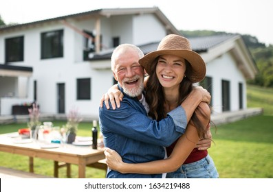 Senior father with daughter outdoors in backyard, looking at camera.