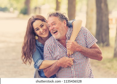 Senior father embraced by his adult daughter, smiling and laughing together in the park outdoors. Happy family moments, father and daughter relationship concept