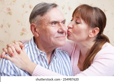 Senior father. Family adult daughter kissing senior father. Elderly man with her caregiver at home.