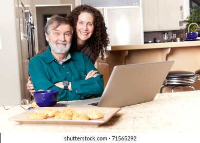 A senior father with his middle age daughter using a laptop