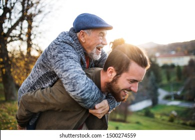 Senior father and his son walking in nature, having fun.