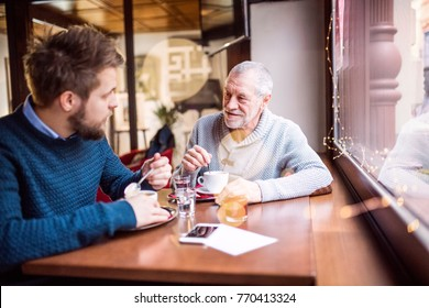 Senior father and his young son in a cafe.