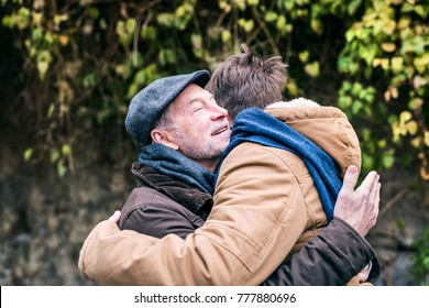 Senior father and his young son on a walk, hugging.