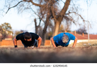 Senior father and son doing pushups on outdoor workout