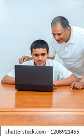Senior Father and teenage son using laptop. Boy and dad with deeper skin tones working with computer. Happy family old grandfather and grandson on laptop.Elderly teacher trainer and teen pupil boy.