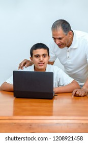 Senior Father and teenage son using laptop. Boy and dad with deeper skin tones working computer. Happy family old grandfather and grandson on laptop. Old teacher and teen boy sitting at wood table.