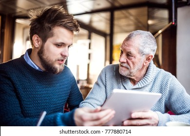 Senior father and young son with tablet in a cafe.