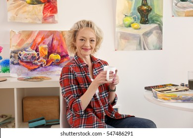 Senior female artist drinking coffee in studio