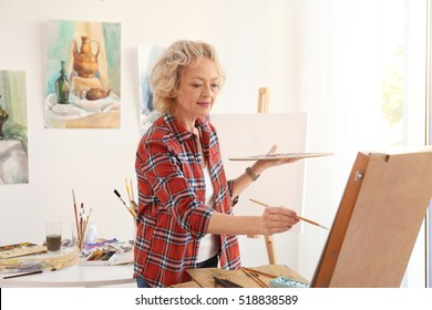 Senior female artist painting picture in studio