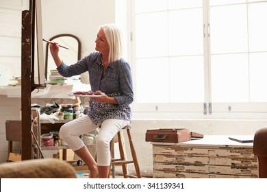 Senior Female Artist Working On Painting In Studio