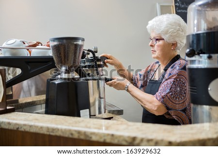 Senior female barista making coffee in cafe