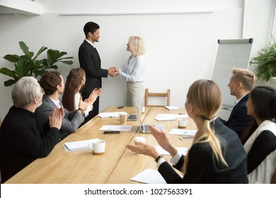 Senior female boss promoting male african employee while team applauding congratulating, aged businesswoman executive and black businessman shaking hands at group meeting, appreciation or recognition