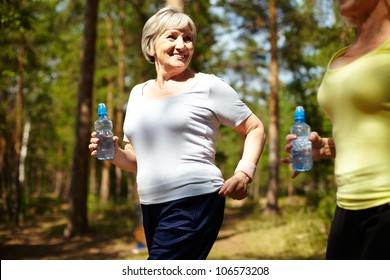 Senior female with bottle of water running outdoors