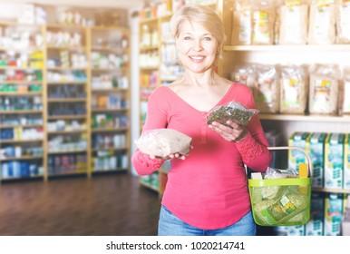 Senior female customer showing purchased healthy food in bio food shop