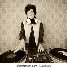 senior female dj mixes on her turntables