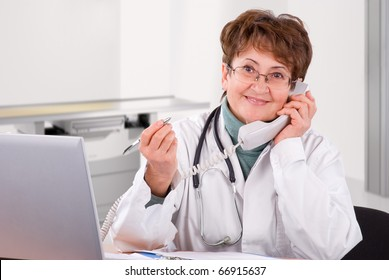Senior female doctor calling on phone, smiling.