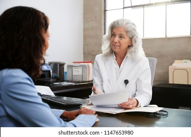 Senior female doctor in consultation with patient in office