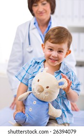 Senior female doctor examining happy child, smiling.