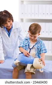 Senior female doctor examining little child boy.