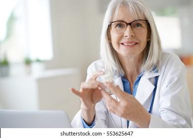 Senior female doctor giving prescription to patient