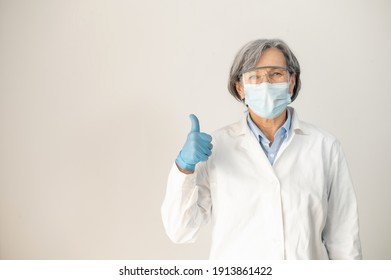 Senior female doctor in medical robe,protective goggles, face mask, and latex gloves, posing isolated over gray background, showing thumb-up, fully equipped health professional working during pandemic