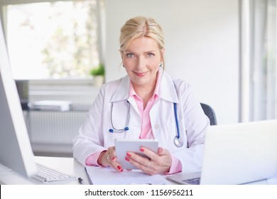 Senior female doctor using touchpad while sitting at doctor's room in front of laptop and computer.