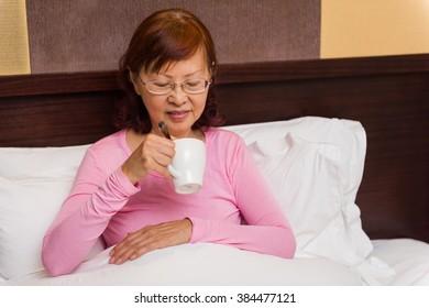 Senior female drinking tea in bed.