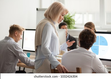 Senior female executive boss supervising computer work of young employee, serious aged woman mentor teaching intern explaining statistics data analysis, older leader helping colleague with problem