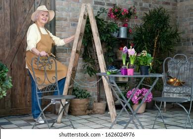 Senior female gardener working in the backyard near the house