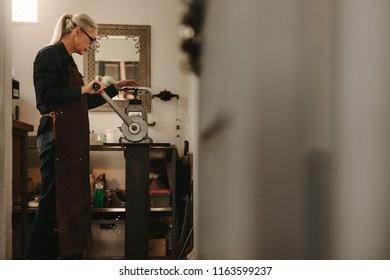 Senior female goldsmith crafting metal on rolling machine in workshop. Mature woman working in goldsmith workshop.