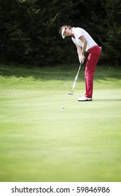 Senior female golf player putting on green with forest in the background, with free space for text.