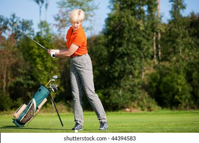 Senior female golfer doing a golf stroke, she is playing on a wonderful summer afternoon